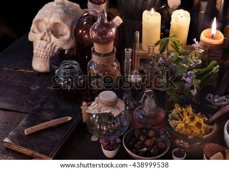 Mystic still life with skull, candles, herbs and vintage bottles. Old pharmacy, esoteric or alternative medicine concept. Black magic and occult objects, medieval alchemist or homeopathic ritual - stock photo