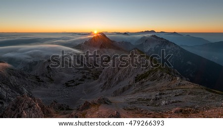 Mystic sunrise with rolling fog in the mountains. Mountain scenery from the Alps.