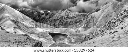Mystical black lake in snowy mountains of Caucasus.Panorama. - stock photo