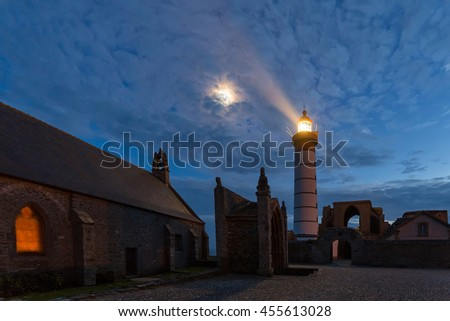 Mystical church and lighthouse illuminated with moon over cloudy sky at Saint Mathieu point, Brittany, France - stock photo