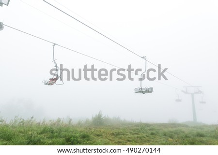 Mystical empty chair lift in the fog