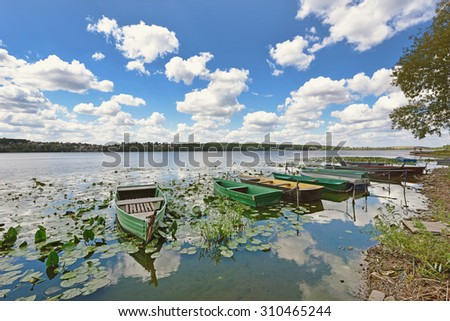 Mystical landscape with boats among water lilies on a pond on a background of clouds (idyll, meditation, anti-stress, rest - concept) - stock photo