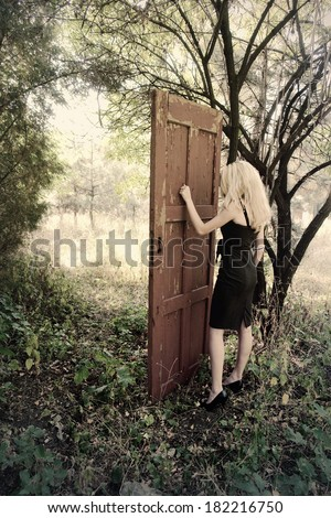 Mystical place. Girl in front of the magic door in the forest        - stock photo