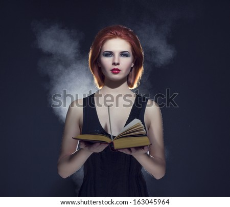 Mystical portrait of a beautiful woman with a book in his hands. - stock photo