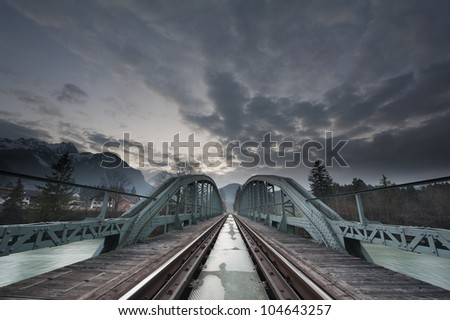 mystical train bridge made of steel and dramatic sky at sunset