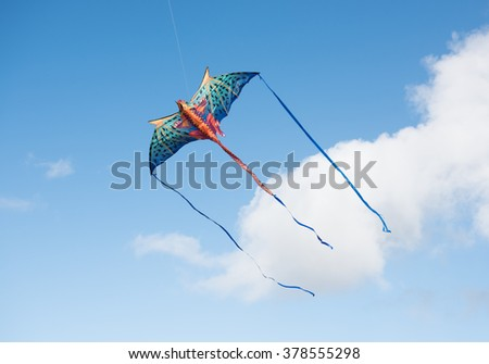 Mythical dragon kite flying in a cloudy sky on a bright sunny day