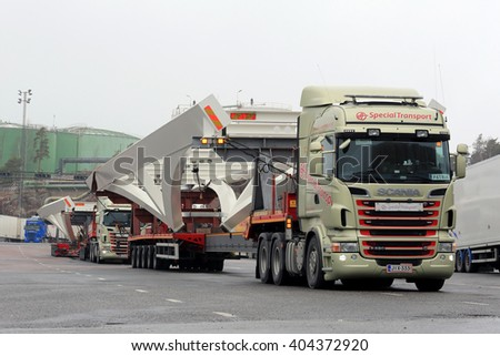 NAANTALI, FINLAND - APRIL 9, 2016: Two Scania R620 trucks which haul  long industrial objects on drop deck trailer as oversize load are parked on a yard. The length of the vehicle is 42 meters. - stock photo