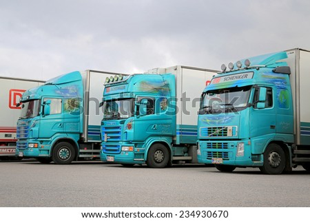 NAANTALI, FINLAND - OCTOBER 11, 2014: Fleet of three colorful trailer trucks on a yard. According to Statistic Finland, a total of 67 million tonnes of goods were transported by lorries in Q2/2014.