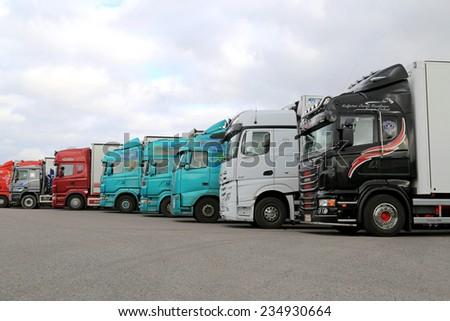 NAANTALI, FINLAND - OCTOBER 11, 2014: Row of trailer trucks on a yard. According to Statistic Finland, a total of 67 million tonnes of goods were transported by lorries in Q2/2014. - stock photo