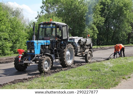 NABEREZHNYE CHELNY - JUNE 2, 2015: Road repairing on Gabdully Tukaya embankment. Men at work.
