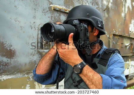 NACHAL OZ,ISR - APR 09 2008:Photojournalist documenting war and conflict.Hundreds of journalists, photographers and cameraman in the world have been killed, injured, kidnapped, threatened or sued. - stock photo