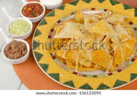Nachos - Cheesy nachos served with sour cream, refried beans, salsa and guacamole dips on a colorful background. - stock photo