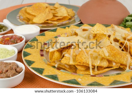 Nachos - Cheesy nachos served with sour cream, refried beans, salsa, jalapenos and guacamole on a colorful background. - stock photo