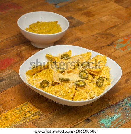 Nachos chips with cheese and jalapenos in a white bowl and fresh guacamole - stock photo