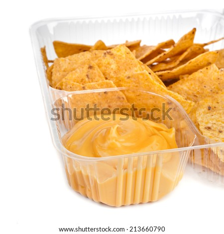 nachos chips with cheese sauce in plastic container close up  isolated on white background - stock photo