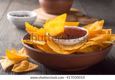 Nachos chips with spicy tomato sauce on a wooden table. - stock photo