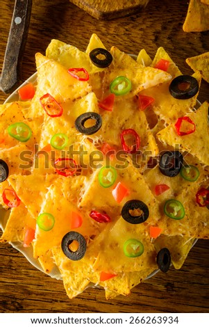 nachos closeup with cheese, olives and chili peppers on a plate - stock photo