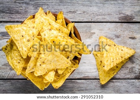 nachos corn chips in a bowl on a wooden table - stock photo