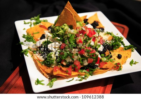 Nachos covered in chicken & cheese, shot with a shallow depth of field - stock photo