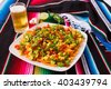 Nachos salad and beer in a square plate over a colored poncho - stock photo