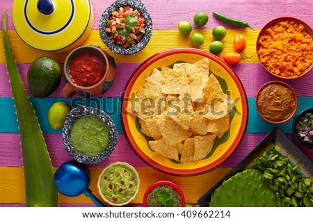 Nachos tortilla chips with mexican sauces on colorful table - stock photo