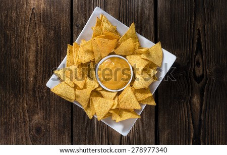 Nachos with Cheese Sauce (close-up shot) on wooden background - stock photo