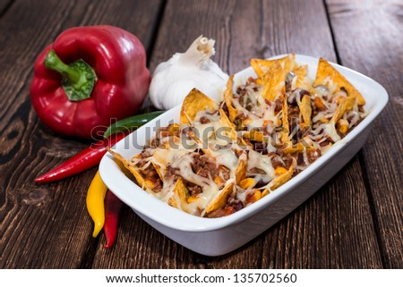 Nachos with Chili con Carne gratinated with cheese - stock photo