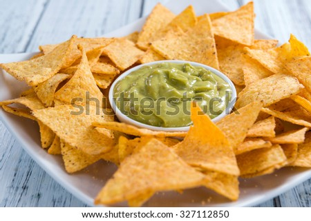 Nachos with Guacamole (close-up shot) on wooden background