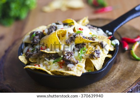 Nachos with haggis, melted cheese and chilli peppers  - stock photo