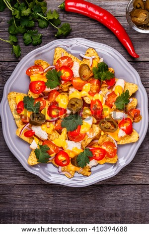Nachos with melted cheese sauce, jalapeno, chicken and vegetables on dark wooden background. - stock photo