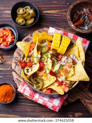 Nachos with melted cheese sauce, salsa and corn cobs in bowl on brown wooden background Top view - stock photo