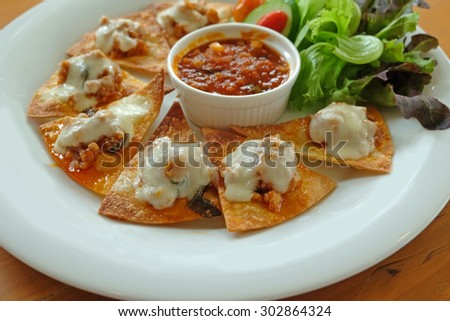 Nachos with pork and cheese topping serve with sauce and salad - stock photo
