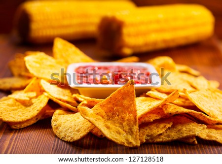 nachos with salsa on wooden table - stock photo