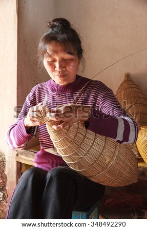 NADINH, VIETNAM December 6, 2015: Unknown woman weaving bamboo fish traps. Weaving these tools are used to catch fish is a traditional occupation in the province NAMDINH.