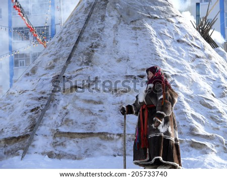 Nadym, Russia - March 15, 2008: the National Nenets accommodation in a modern city in Nadym, Russia - March 15, 2008. Unknown woman the Nenets woman with a cane is passing a house.