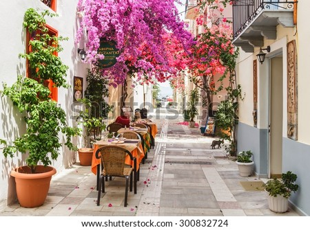NAFPLION, GREECE- JUNE 11: Outdoor restaurant in the narrow streets of  Nafplion town with beautiful Bougainvillea flowers, Nafplion, Greece on June 11, 2015.