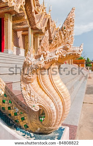 Naga statue infront of Thai style golden castle, Thailand.