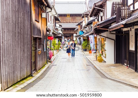 Nagahama, Japan - August 6, 2015: People stroll the empty traditional streets of Nagahama among tourist shops in front of Daitsu-ji Buddhist temple, Japan. Horizontal