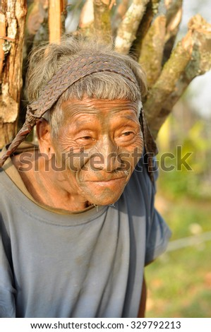 Nagaland, India - March 2012: Old man carries heavy load in Nagaland, remote region of India. Documentary editorial.