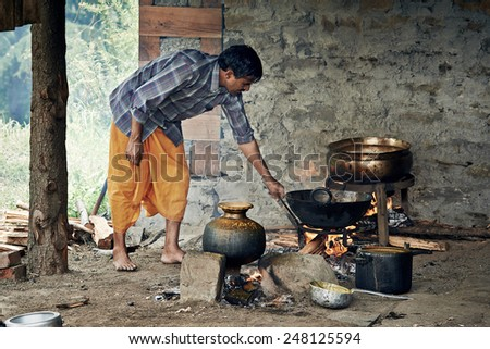 NAGGAR, INDIA - JULY 17: Cooking indian. Hindu man preparing food for a traditional wedding ceremony on July 17, 2013. Naggar, Kullu Valley, Himachal Pradesh, India.