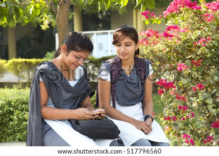 NAGPUR, MAHARASHTRA, INDIA, 9 APRIL 2016 : unidentified young girl students Surfing the net outdoors and working on laptop and smiling while sitting together on the outdoors staircase at campus.
