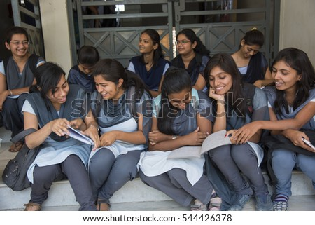 NAGPUR, MAHARASHTRA, INDIA, 11 APRIL 2016 : unidentified young university students talking together about their studies project on the outdoors staircase at university campus.