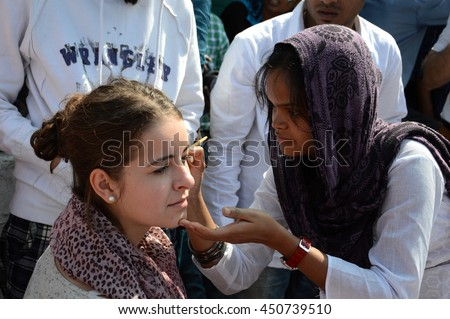NAGPUR, MAHARASHTRA, INDIA, JANUARY - 26 : Artist painting Indian Flag on face of foreigner girl on the occasion of Indian Republic Day at Nagpur. Republic Day Celebration on 26 January 2014