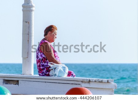 Nahariya, Israel - May 30, 2016: Elderly woman relaxing at sunset on the beach in Nahariya, Israel