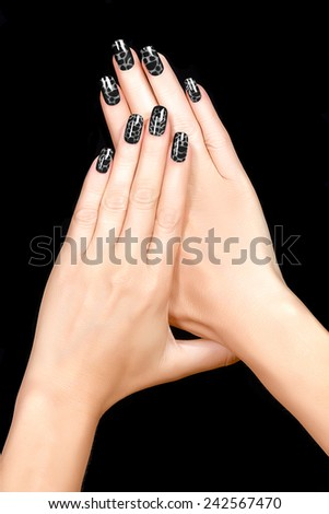 Nail Art. Trendy crackle nail polish in black. Manicure and nail tattoo trend. Closeup of woman hands isolated on black background - stock photo