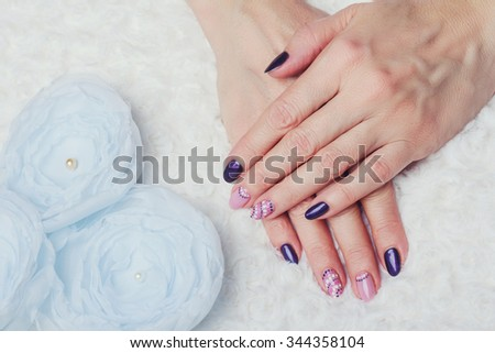 Nail art with purple and pink colors on silk flowers background