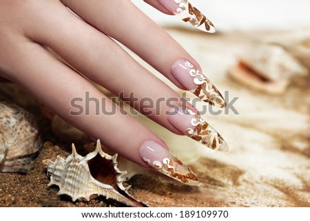 Nail design with brown and white these little shells inside gel nails on the background of shells and sand. - stock photo