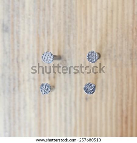 nail head set on wood background - stock photo