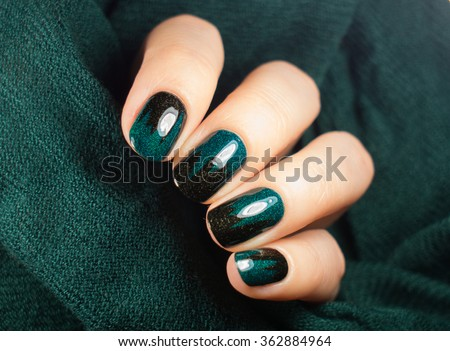 Nail polish in hand, beautiful green manicure with black texture - stock photo