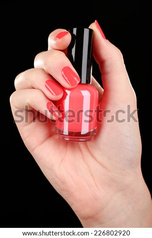 Nail polish in hand, close-up - stock photo